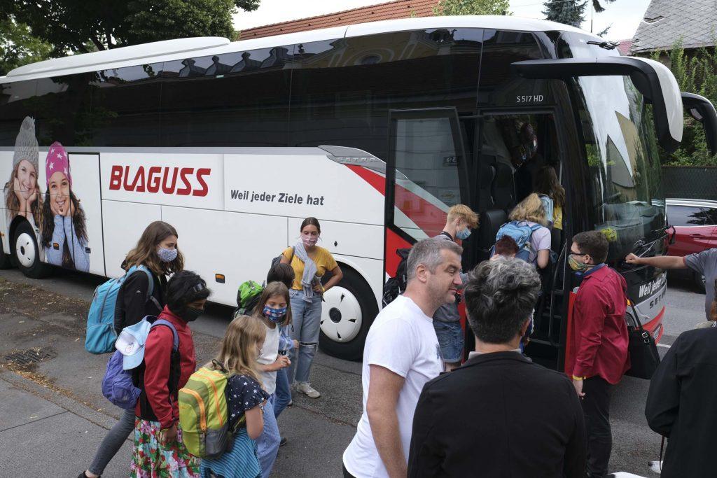 Lagerlinge steigen mit Masken in den Bus ein (2020)