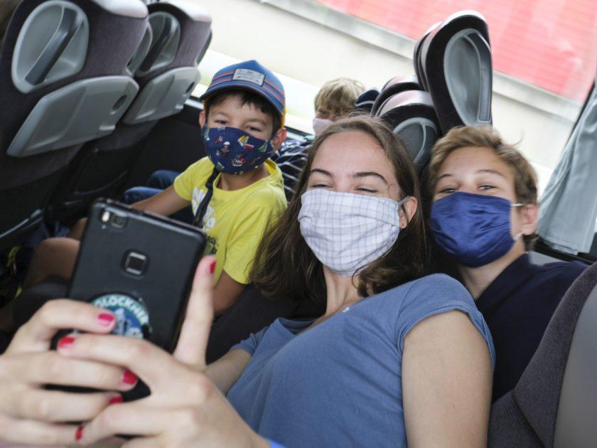 Betreuerin und zwei Lagerlinge machen mit Smartphone bei der Hinfahrt im Bus ein Selfie
