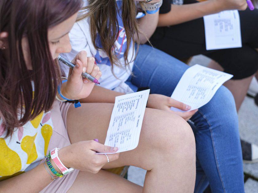 Kinder sitzen auf Bank und schreiben auf Zettel