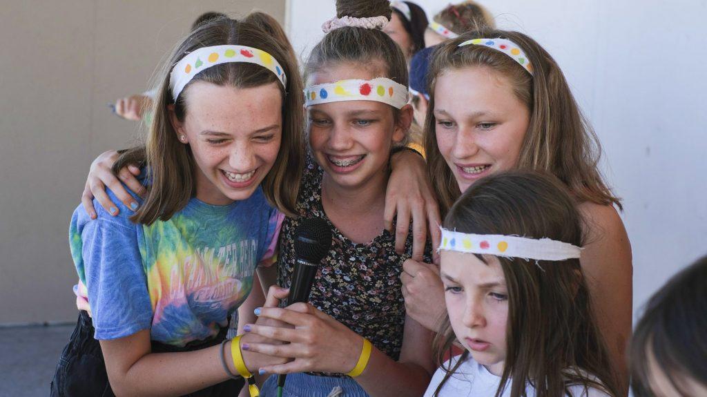 vier Mädchen singen erfreut Karaoke in ein Mikrofon bei einem Programmpunkt auf Sommerlager